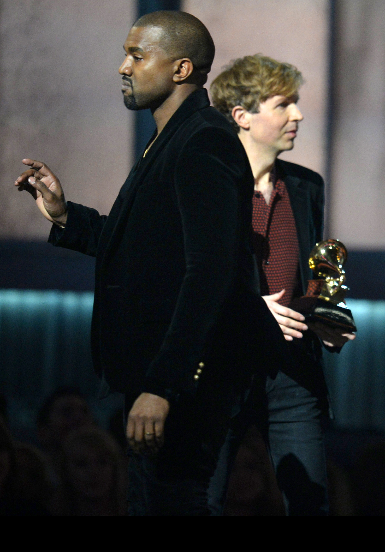 (FILES) In this February 8, 2015 file photo, winner for Album Of The Year Beck reacts as Kanye West appears on stage at the 57th Annual Grammy Awards in Los Angeles February 8, 2015. West on February 11, 2015 urged an overhaul of the Grammys to award commercially successful musicians, even as the rapper toned down his criticism of this year's surprise winner Beck. The famously mercurial West stole the spotlight at the music industry's awards night Sunday when he rushed toward the stage as Beck -- the innovative rocker who has enjoyed critical acclaim, if a niche following, for two decades --accepted the Album of the Year award for his lush, melancholy  Morning Phase.  Soon after the broadcast, West said that Beck should  respect artistry  and give his award to superstar Beyonce for her self-titled album, one of her most intense works which features the ode to marital bliss  Drunk In Love  sung with husband Jay-Z.  AFP PHOTO / ROBYN BECK / FILES